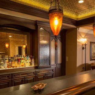 Expansive traditional single-wall home bar in Philadelphia with raised-panel cabinets, dark wood cabinets, marble worktops, porcelain flooring, brown floors and brown worktops.