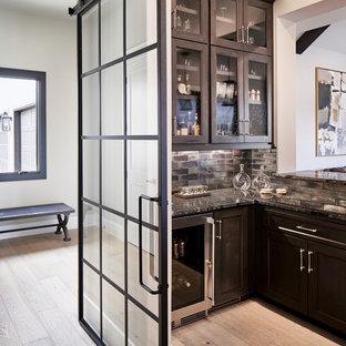 Idéer för en klassisk bruna l-formad hemmabar med vask, med en undermonterad diskho, luckor med infälld panel, skåp i mörkt trä, granitbänkskiva, brunt stänkskydd, stänkskydd i keramik och ljust trägolv