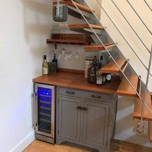 ニューヨークの小さいコンテンポラリースタイルのおしゃれなホームバー (I型、シンクなし、グレーのキャビネット、木材カウンター、白いキッチンパネル、竹フローリング) の写真