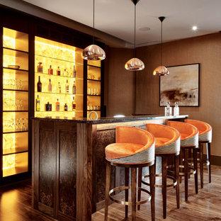 ロンドンのトランジショナルスタイルのおしゃれな着席型バー (ll型、シェーカースタイル扉のキャビネット、中間色木目調キャビネット、無垢フローリング、茶色い床、マルチカラーのキッチンカウンター) の写真