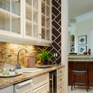 Photo of a small traditional single-wall wet bar in Miami with a built-in sink, glass-front cabinets, white cabinets, granite worktops, beige splashback, glass tiled splashback and travertine flooring.