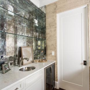 Foto di un piccolo armadio bar tropicale con lavello sottopiano, ante a filo, ante bianche, top in marmo, paraspruzzi grigio, paraspruzzi a specchio, parquet scuro e pavimento marrone