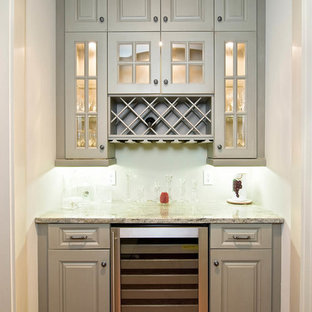 Small traditional single-wall wet bar in Cleveland with raised-panel cabinets, grey cabinets, granite worktops, medium hardwood flooring and brown floors.