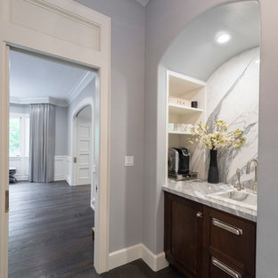 Design ideas for a small traditional single-wall wet bar in Los Angeles with beaded cabinets, dark wood cabinets, marble worktops, white splashback, marble splashback, dark hardwood flooring, brown floors, a built-in sink and grey worktops.