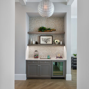 Cette image montre un petit bar de salon avec évier linéaire traditionnel avec aucun évier ou lavabo, un placard avec porte à panneau encastré, des portes de placard grises, un plan de travail en quartz modifié, une crédence multicolore, une crédence en mosaïque et un sol en bois clair.