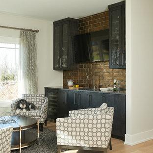 グランドラピッズの中くらいのトランジショナルスタイルのおしゃれなウェット バー (I型、アンダーカウンターシンク、人工大理石カウンター、茶色いキッチンパネル、淡色無垢フローリング、黒いキャビネット、ガラス扉のキャビネット、メタルタイルのキッチンパネル、グレーのキッチンカウンター、茶色い床) の写真