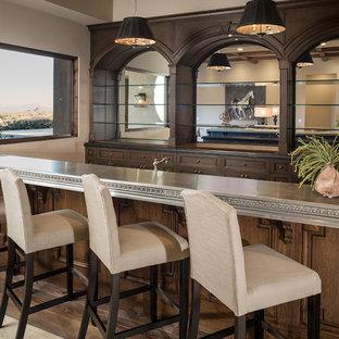 Ispirazione per un ampio angolo bar con lavandino mediterraneo con lavello da incasso, ante con riquadro incassato, ante in legno bruno, top in zinco, pavimento beige e top grigio