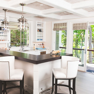 Photo of a beach style breakfast bar in Boston with a submerged sink, glass-front cabinets, white cabinets, light hardwood flooring, beige floors and brown worktops.