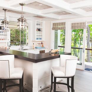 ボストンのビーチスタイルのおしゃれな着席型バー (アンダーカウンターシンク、ガラス扉のキャビネット、白いキャビネット、淡色無垢フローリング、ベージュの床、茶色いキッチンカウンター) の写真