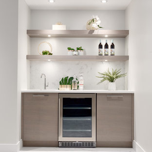 This is an example of a medium sized contemporary single-wall wet bar in Vancouver with a submerged sink, flat-panel cabinets, light wood cabinets, marble worktops, white splashback, marble splashback, carpet, beige floors and white worktops.