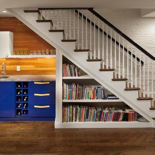 Idée de décoration pour un petit bar de salon avec évier linéaire bohème avec un évier encastré, un placard à porte plane, des portes de placard bleues, un plan de travail en marbre, une crédence en bois et un sol en bois brun.