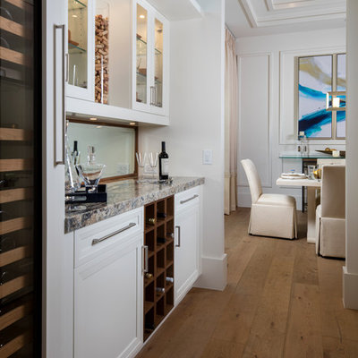 Example of a beach style single-wall medium tone wood floor home bar design in Miami with no sink, glass-front cabinets, white cabinets, mirror backsplash and multicolored countertops