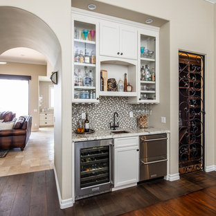 Photo of a medium sized traditional single-wall wet bar in San Diego with a submerged sink, recessed-panel cabinets, white cabinets, granite worktops, multi-coloured splashback, mosaic tiled splashback, dark hardwood flooring, brown floors and multicoloured worktops.