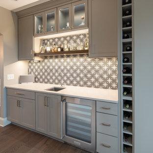 Ispirazione per un angolo bar con lavandino classico di medie dimensioni con lavello sottopiano, ante in stile shaker, ante grigie, paraspruzzi grigio, paraspruzzi con piastrelle di cemento, pavimento in legno massello medio, pavimento marrone e top bianco