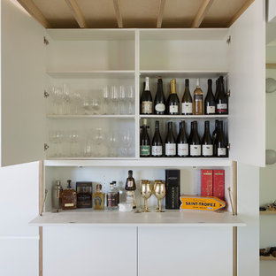 Photo of a contemporary single-wall wet bar in Sydney with flat-panel cabinets, white cabinets, white splashback and white benchtop.