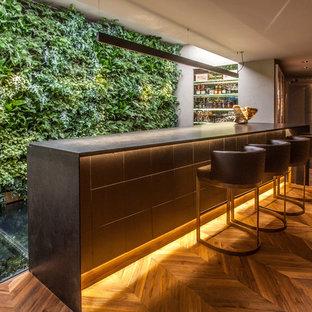 ニューヨークのコンテンポラリースタイルのおしゃれな着席型バー (シンクなし、オープンシェルフ、無垢フローリング、茶色い床、黒いキッチンカウンター) の写真