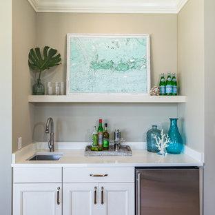 Diseño de bar en casa con fregadero lineal, costero, con fregadero bajoencimera, armarios con paneles empotrados, puertas de armario blancas, suelo de madera clara y encimeras blancas