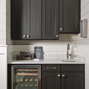 Modelo de bar en casa con fregadero lineal, tradicional renovado, con fregadero bajoencimera, armarios estilo shaker, puertas de armario marrones, suelo de madera oscura y suelo marrón