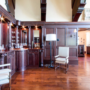 Inspiration for a large timeless l-shaped medium tone wood floor and brown floor wet bar remodel in Milwaukee with furniture-like cabinets, dark wood cabinets, wood countertops, brown backsplash, wood backsplash and multicolored countertops