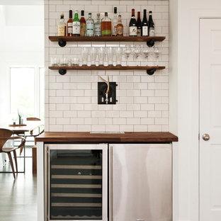 ニューヨークの小さいトランジショナルスタイルのおしゃれなホームバー (木材カウンター、白いキッチンパネル、セラミックタイルのキッチンパネル、濃色無垢フローリング、I型、茶色いキッチンカウンター) の写真
