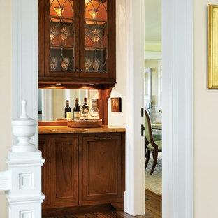 Esempio di un piccolo angolo bar stile marino con ante con riquadro incassato, ante in legno scuro, top in granito, paraspruzzi a specchio e pavimento in legno massello medio