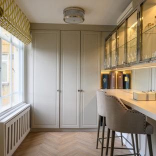 Photo of a medium sized contemporary l-shaped breakfast bar in London with raised-panel cabinets, grey cabinets, mirror splashback, medium hardwood flooring, beige floors and grey worktops.