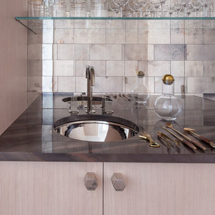 This is an example of a medium sized contemporary single-wall wet bar in New York with a submerged sink, flat-panel cabinets, light wood cabinets, marble worktops, grey splashback, mirror splashback, light hardwood flooring and brown worktops.