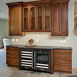 ミネアポリスの中くらいのトラディショナルスタイルのおしゃれなウェット バー (レイズドパネル扉のキャビネット、中間色木目調キャビネット、グレーのキッチンパネル、セメントタイルのキッチンパネル、磁器タイルの床、グレーの床、I型、御影石カウンター、グレーのキッチンカウンター) の写真