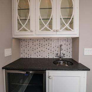 シカゴの小さいおしゃれなウェット バー (御影石カウンター、I型、アンダーカウンターシンク、ガラス扉のキャビネット、マルチカラーのキッチンパネル、ボーダータイルのキッチンパネル、濃色無垢フローリング、白いキャビネット) の写真