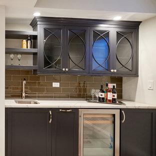 Esempio di un piccolo angolo bar con lavandino chic con lavello sottopiano, ante con riquadro incassato, ante grigie, top in granito, paraspruzzi grigio, paraspruzzi con piastrelle di vetro e pavimento in gres porcellanato