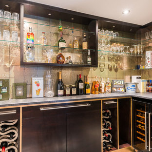 Design ideas for a small contemporary l-shaped home bar in Berkshire with flat-panel cabinets, black cabinets, ceramic flooring, grey floors, grey splashback and grey worktops.