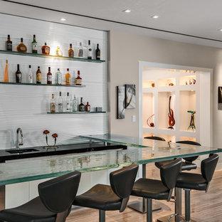 Idee per un grande angolo bar con lavandino minimal con lavello sottopiano, top in vetro, paraspruzzi bianco, pavimento in gres porcellanato e pavimento beige