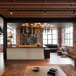 This is an example of a mid-sized industrial u-shaped seated home bar in Melbourne with an undermount sink, glass-front cabinets, light wood cabinets, onyx benchtops, brick splashback, medium hardwood floors, brown floor and brown benchtop.