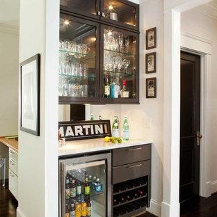 Immagine di un angolo bar minimal di medie dimensioni con ante nere, top in marmo, paraspruzzi a specchio, parquet scuro, top bianco e ante di vetro