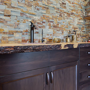 カルガリーの小さいトラディショナルスタイルのおしゃれな着席型バー (アンダーカウンターシンク、シェーカースタイル扉のキャビネット、濃色木目調キャビネット、木材カウンター、マルチカラーのキッチンパネル、石タイルのキッチンパネル、リノリウムの床、茶色い床) の写真