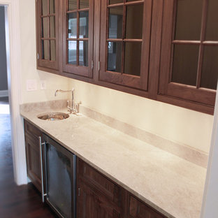 Medium sized classic single-wall wet bar in Chicago with a submerged sink, beaded cabinets, dark wood cabinets, marble worktops, beige splashback, marble splashback, dark hardwood flooring and brown floors.