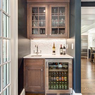 ワシントンD.C.の小さいトランジショナルスタイルのおしゃれなウェット バー (I型、アンダーカウンターシンク、ガラス扉のキャビネット、中間色木目調キャビネット、クオーツストーンカウンター、白いキッチンパネル、石タイルのキッチンパネル、無垢フローリング、茶色い床、白いキッチンカウンター) の写真