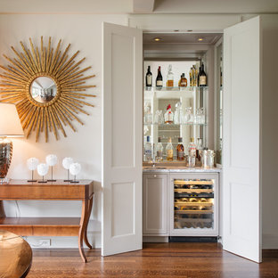 Small traditional single-wall wet bar in San Francisco with medium hardwood flooring, a submerged sink, recessed-panel cabinets, grey cabinets, mirror splashback, brown floors and white worktops.