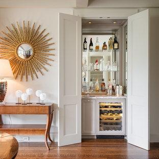 Ispirazione per un piccolo armadio bar chic con pavimento in legno massello medio, lavello sottopiano, ante con riquadro incassato, ante grigie, paraspruzzi a specchio, pavimento marrone e top bianco
