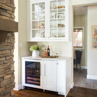 セントルイスの小さいカントリー風おしゃれなホームバー (白いキャビネット、クオーツストーンカウンター、白いキッチンパネル、茶色い床、白いキッチンカウンター、I型、シンクなし、ガラス扉のキャビネット、サブウェイタイルのキッチンパネル、濃色無垢フローリング) の写真