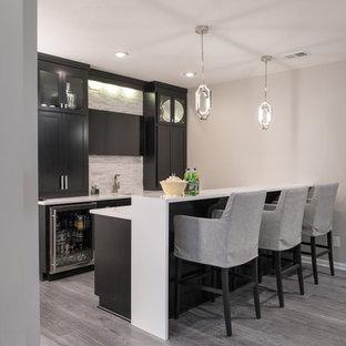 カンザスシティの広いトランジショナルスタイルのおしゃれな着席型バー (I型、アンダーカウンターシンク、落し込みパネル扉のキャビネット、黒いキャビネット、クオーツストーンカウンター、白いキッチンパネル、ボーダータイルのキッチンパネル、クッションフロア、グレーの床) の写真