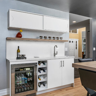 Large trendy single-wall medium tone wood floor and brown floor wet bar photo in Detroit with an undermount sink, flat-panel cabinets, white cabinets, quartz countertops, white backsplash, stone slab backsplash and white countertops