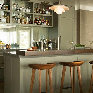 Idee per un bancone bar costiero con ante in stile shaker, ante verdi, top in legno, paraspruzzi a specchio, pavimento in legno massello medio, pavimento marrone e top marrone