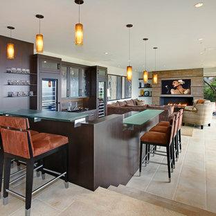 オレンジカウンティの巨大なコンテンポラリースタイルのおしゃれな着席型バー (コの字型、濃色木目調キャビネット、ガラスカウンター、シェーカースタイル扉のキャビネット、茶色いキッチンパネル、木材のキッチンパネル、セラミックタイルの床、ベージュの床) の写真