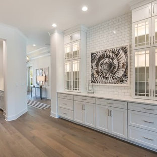 Example of a mid-sized cottage single-wall light wood floor and brown floor home bar design in Jacksonville with no sink, glass-front cabinets, white cabinets, quartz countertops, white backsplash, subway tile backsplash and white countertops