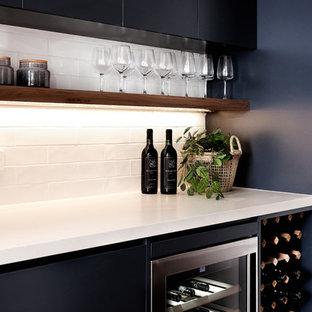 シドニーの中くらいのビーチスタイルのおしゃれなホームバー (フラットパネル扉のキャビネット、クオーツストーンカウンター、白いキッチンパネル、白いキッチンカウンター、サブウェイタイルのキッチンパネル、I型、黒いキャビネット) の写真