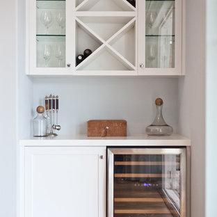 Esempio di un piccolo angolo bar stile marinaro con ante bianche, top in laminato e pavimento in legno massello medio