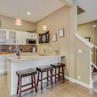 カルガリーの小さいコンテンポラリースタイルのおしゃれな着席型バー (ll型、ドロップインシンク、シェーカースタイル扉のキャビネット、白いキャビネット、ラミネートカウンター、マルチカラーのキッチンパネル、ガラス板のキッチンパネル、セラミックタイルの床、ベージュの床、白いキッチンカウンター) の写真