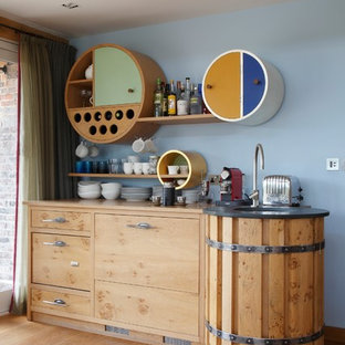 This is an example of a small urban single-wall home bar in Hampshire with a submerged sink, flat-panel cabinets, light wood cabinets and light hardwood flooring.