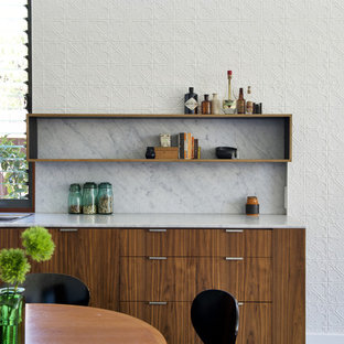 This is an example of a midcentury home bar in Perth with flat-panel cabinets and marble splashback.